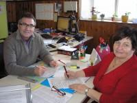 Pfarrer MMag. Marek Duda, links im Bild und Helga Eder, rechts im Bild, an einem Tisch sitzend. Jeder mit einer Liste und einem Bleistift in der Hand und in die Kamera blickend.