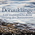 """Abb. eines Gewässers mit Kiesbett im Vordergund. Im Vordergrund die Schriftzüge """"Donauklänge"""" und """"Eine musikalische Reise entlang des Donaustroms"""""""