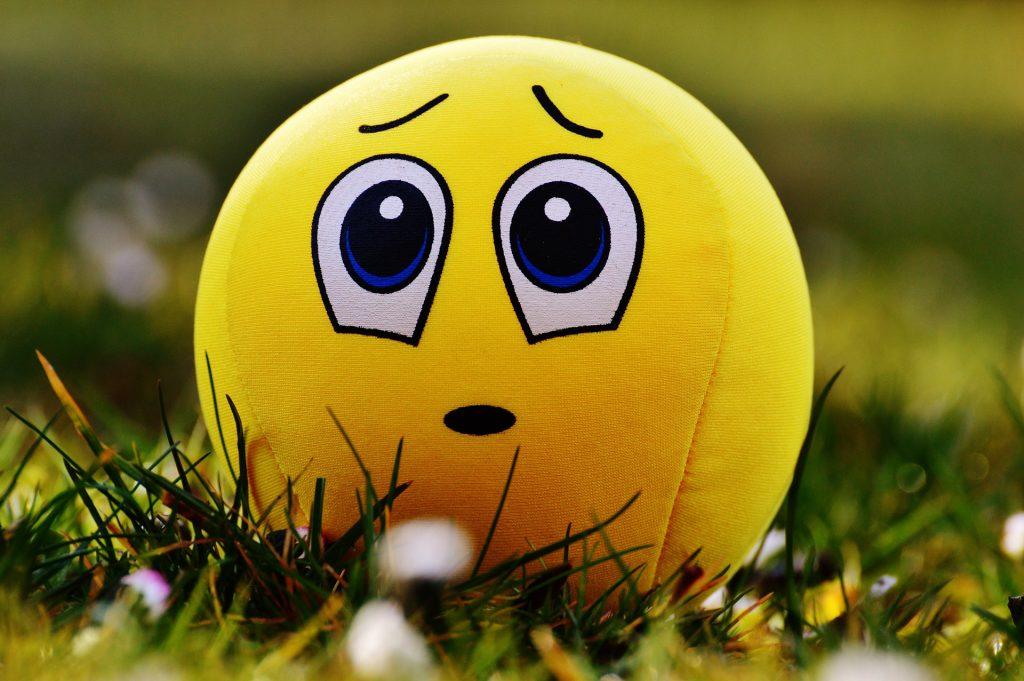 Unglücklicher Smiley als Stoffball in der Wiese