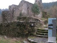 Vier Stufen umgeben von Steinmauern führen in das Innere der Ruiine des Burgkircherls